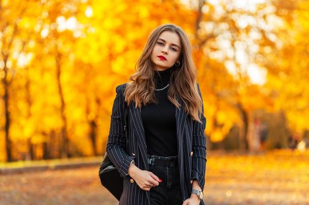 Herfst portret van een mooie jonge vrouw met rode lippen in een zwart elegant pak met een blazer en trui loopt in het park met gekleurd gouden herfstgebladerte bij zonsondergang
