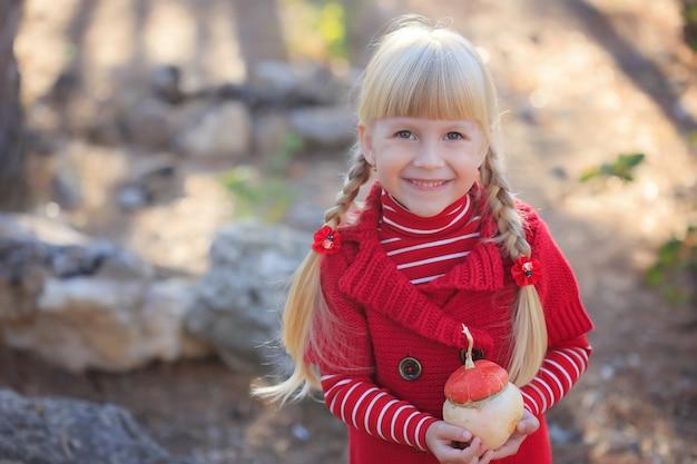 Herfst portret van een schattig meisje met een pompoen.
