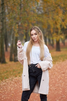 Herfst portret van jonge blonde aantrekkelijke vrouw met lang haar dragen witte overhemd, zwarte moeder jeans, trendy herfst jas wandelen in herfst park.