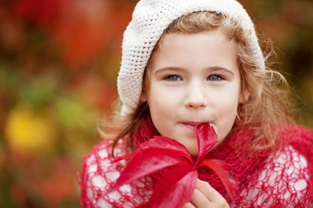 Herfst portret van meisje. mooi klein meisje met rode druivenbladeren in de herfstpark. herfstactiviteiten voor kinderen. halloween en thanksgiving tijd plezier voor familie.
