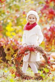 Herfst portret van schattig klein meisje. mooi klein meisje met rode druivenbladeren krans in herfst park.