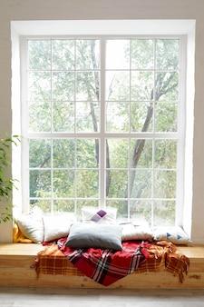 Herfst raam landschap met met plaid en kussens, comfort thuis