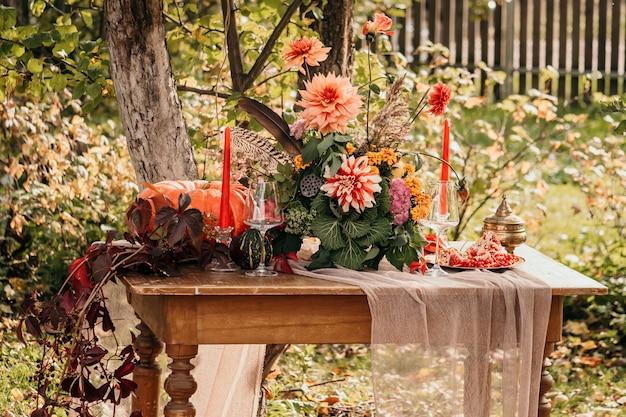 Herfst romantische setting: boeket van dahlia's, granaatappels, kaarsen, pompoenen en glazen