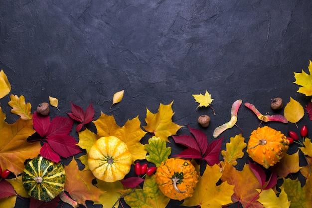 Herfst samenstelling. frame gemaakt van verschillende veelkleurige gedroogde bladeren en pompoen op donkere achtergrond. herfst, herfst concept. plat lag, bovenaanzicht, kopie ruimte