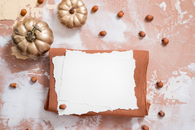 Herfst samenstelling. gouden pompoenen en noten, droge bladeren op een bruine achtergrond. warme gebreide rode trui en sjaal, papieren bladeren en een notitieboekje. trend gescheurd papier.