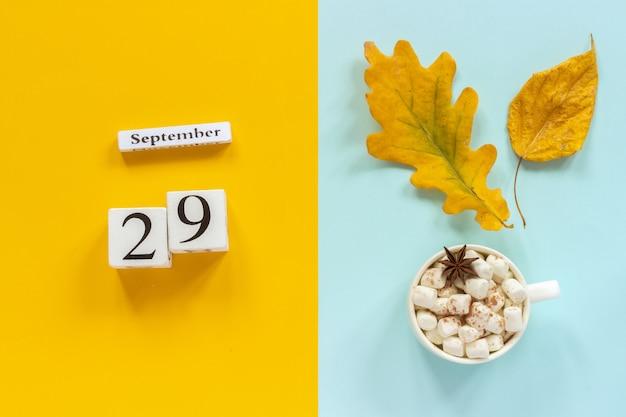 Herfst samenstelling. houten kalender 29 september, kopje cacao met marshmallows en gele herfstbladeren op geel blauw