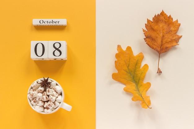 Herfst samenstelling. houten kalender 8 oktober, kopje cacao met marshmallows en gele herfstbladeren op geel beige