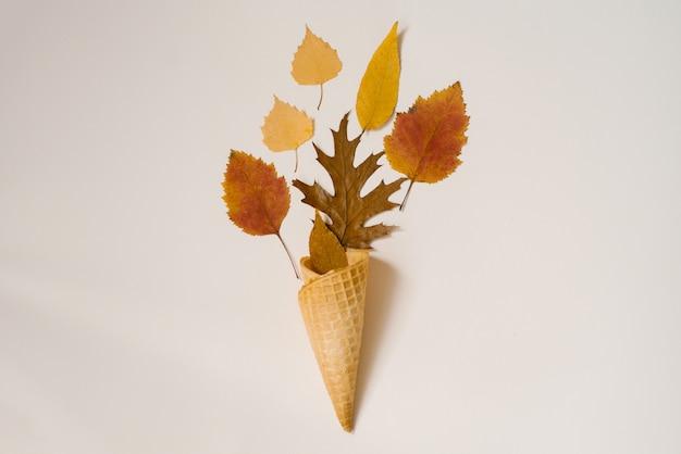 Herfst samenstelling. kegel van wafelijs met droge vergeelde en rode bladeren
