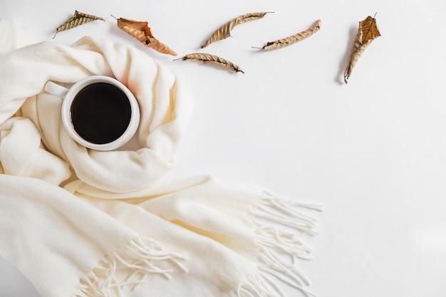 Herfst samenstelling. kop koffie, sjaal en droge bladeren op grijze achtergrond. plat lag, bovenaanzicht, kopie ruimte