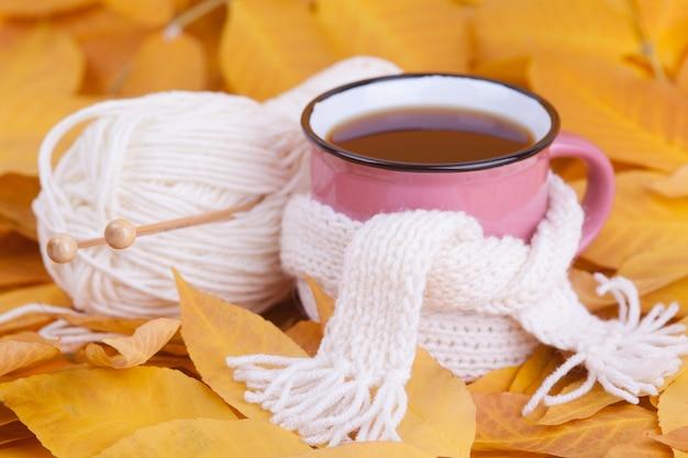 Herfst samenstelling kopje thee verpakt in een sjaal seizoensgebonden ochtend thee stilleven concept
