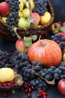 Herfst samenstelling met appels, druiven, pompoen en kornoelje op een donkere achtergrond