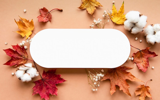 Herfst samenstelling. papier blanco, gedroogde bloemen en bladeren op bruine achtergrond. herfst, herfst concept. plat leggen, bovenaanzicht, kopie ruimte