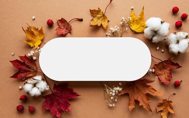 Herfst samenstelling. papier blanco, gedroogde bloemen en bladeren op bruine achtergrond. herfst, herfst concept.