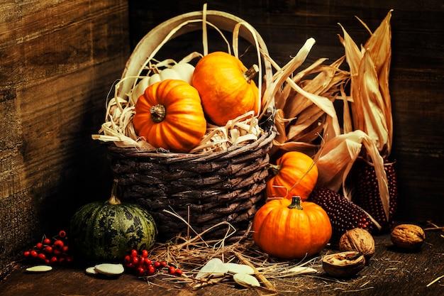 Herfst samenstelling. pompoenen en maïs op oude houten tafel. thanksgiving day concept