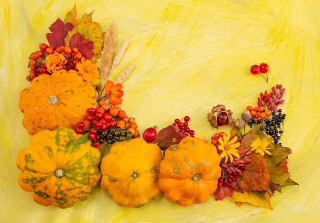 Herfst samenstelling thanksgiving of halloween concept bessen pompoen op een gele achtergrond plat lag