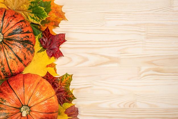 Herfst samenstelling van gevallen bladeren van esdoorn en pompoenen op houten tafel, thanksgiving vakantie partij achtergrond.