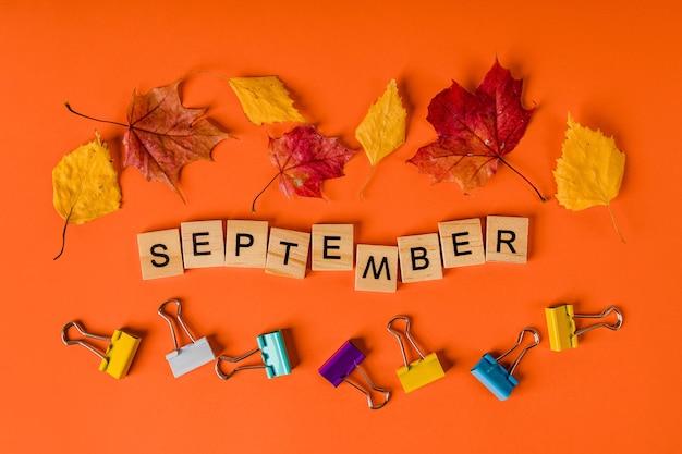 Herfst school achtergrond met bladeren en paperclips woord september is gemaakt van houten letters