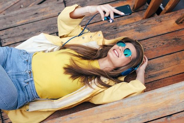 Herfst stad stijl gelukkige vrouw veel plezier op straat luisteren muziek met oortelefoons en haar smartphone