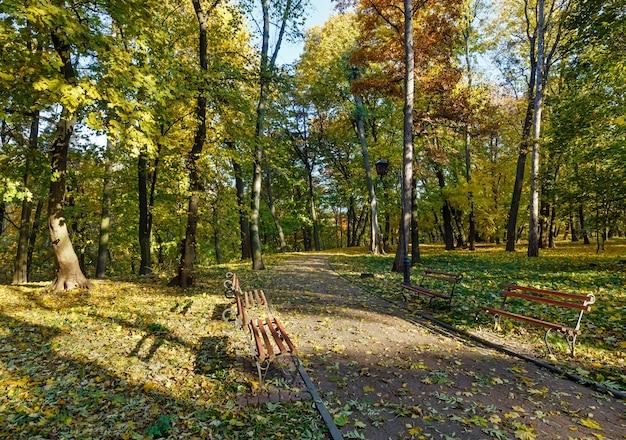 Herfst stadspark met voetpad en bankjes.