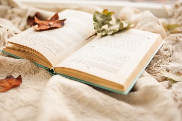 Herfst stilleven. een open boek ligt op een beige tapijt, herfst gevallen bladeren liggen op het boek.