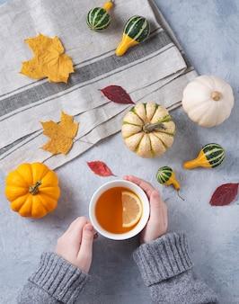 Herfst stilleven. kopje thee in de hand en enkele decoratieve pompoenen en bladeren op blauw.
