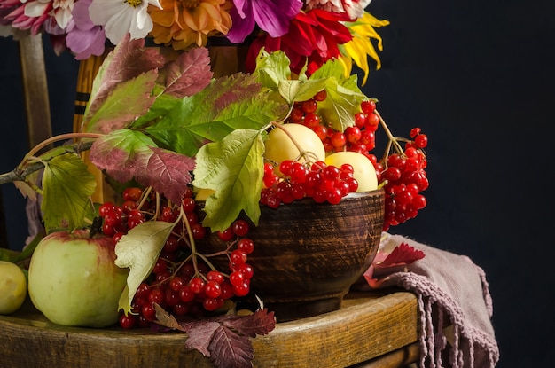 Herfst stilleven met appels, viburnumbessen, herfstbladeren op een vintage houten stoel op een zwart oppervlak