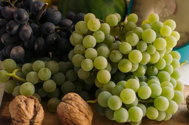 Herfst stilleven met druiven op een houten bord en walnoten rond op een houten witte tafel. op de weegschaal. het concept van de herfstoogst. vrolijke thanksgiving. selectieve aandacht. sjabloon voor ontwerp.
