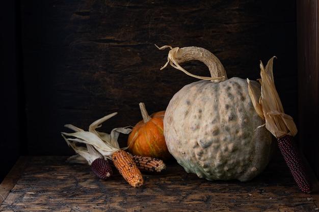 Herfst stilleven met pompoenen en maïs op oude houten tafel.