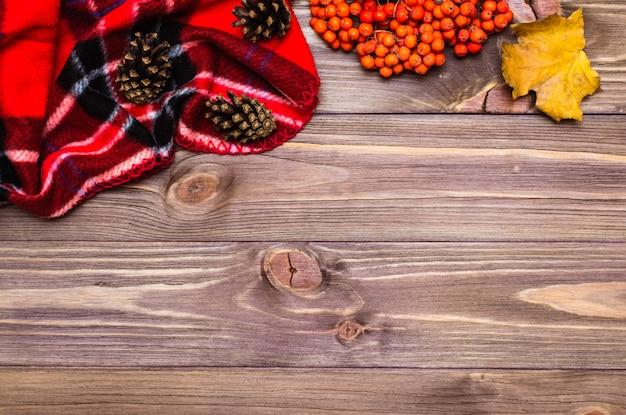 Herfst stilleven plaid, esdoornblad, kegels en rowan op hout