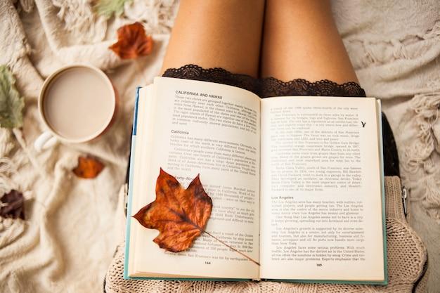 Herfst stilleven. uitzicht van boven. het meisje leest een open boek zittend op een plaid