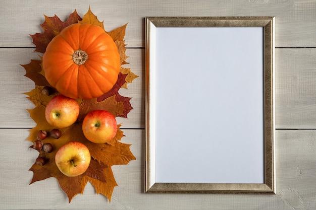 Herfst stilleven van oranje pompoen, appels en esdoorn bladeren op witte houten achtergrond met frame mockup plek voor tekst.