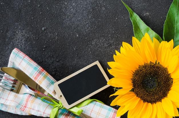 Herfst tabel couvert met lege tag, bestek met servet en zonnebloem.