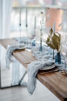 Herfst tafeldecoratie, houten tafel geserveerd met gedroogde bloem, wit bord, vintage bestek, kandelaars met helder blauw gaas tafelkleed bovenaanzicht, selectieve aandacht.