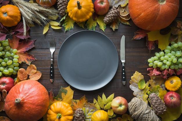Herfst tafelsetting met bladeren en pompoenen, bovenaanzicht