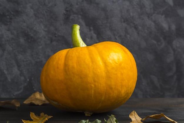 Herfst thanksgiving en halloween-pompoen met droge bladeren op donker. herfst samenstelling.