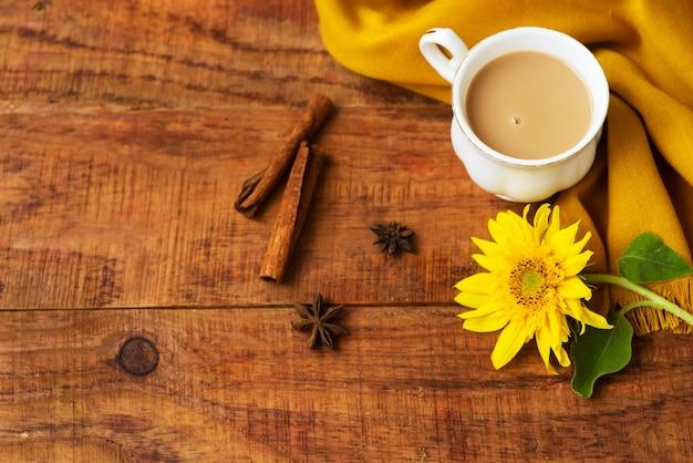 Herfst thee kopje samenstelling met melk, gele sjaals, kaneelstokjes en zonnebloem op een houten achtergrond. herfst achtergrond. warme, gezellige sfeer van de herfst. plat leggen, lay-out. plaats voor tekst, frame