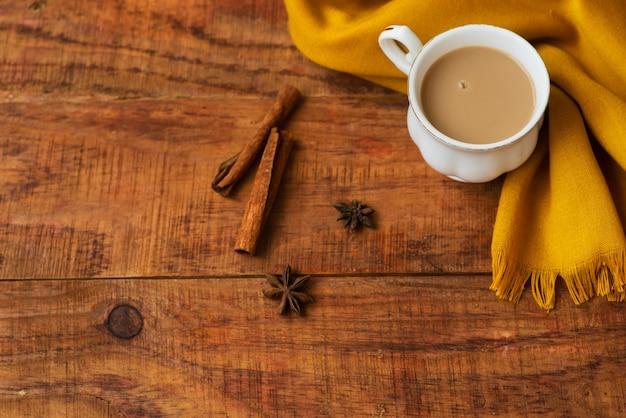 Herfst thee kopje samenstelling met melk, gele sjaals, kaneelstokjes op een houten achtergrond. herfst achtergrond. warme, gezellige sfeer van de herfst. plat leggen, lay-out. plaats voor tekst, frame