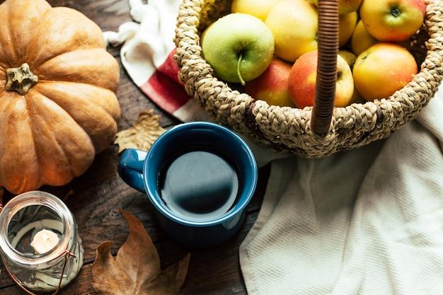 Herfst, thee, pompoenen en appels op een houten tafel