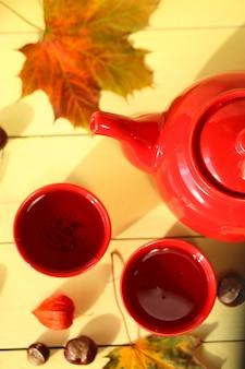 Herfst thee. theepot, kopjes thee, kastanjes, bladeren