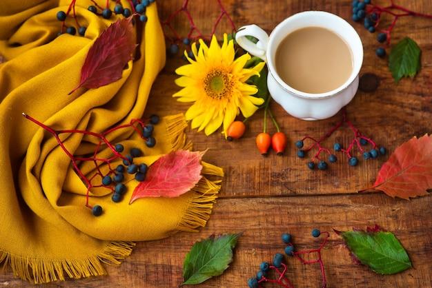 Herfst theekop samenstelling, gele sjaal, rozenbessen en zonnebloembloem op een houten achtergrond