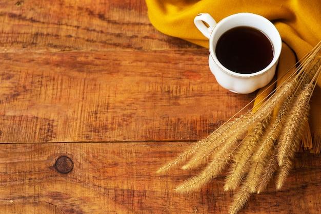 Herfst theekop samenstelling, gele sjaals en aartjes van tarwe op een houten achtergrond