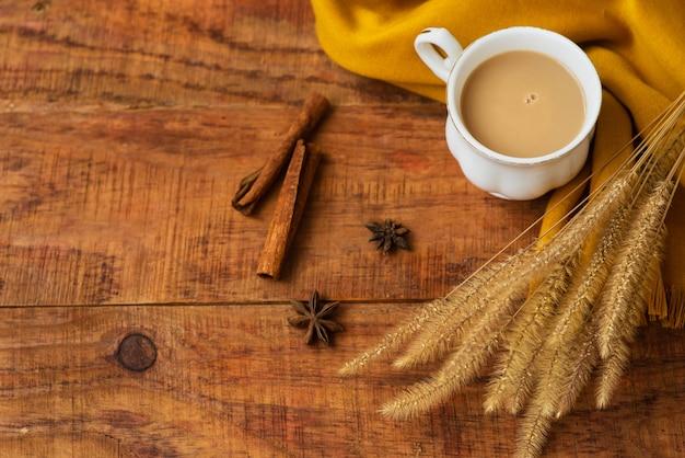Herfst theekop samenstelling met melk, gele sjaals, kaneelstokjes en aartjes van tarwe op een houten achtergrond