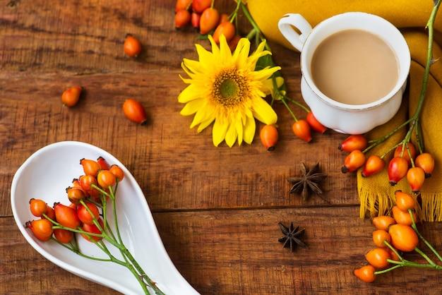 Herfst theekop samenstelling met melk, gele sjaals, zonnebloem en rozenbottels op een houten achtergrond