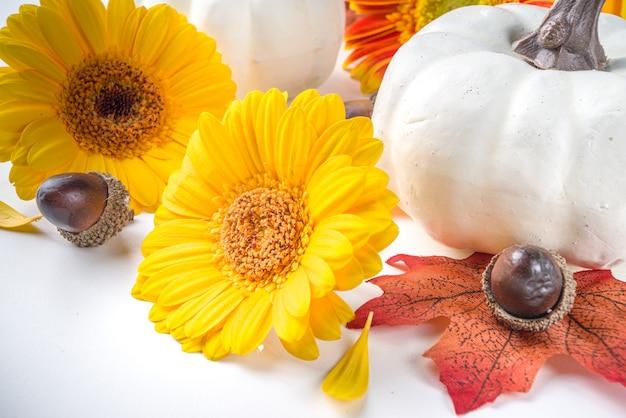 Herfst thema concept. platte lay compositie met kleurrijke bloemen, rode gele bladeren, witte pompoenen op witte achtergrond. bright fall, thanksgiving day concept. platliggend, bovenaanzicht, kopieerruimte