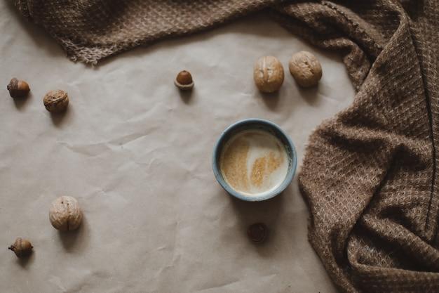 Herfst thema, kopje cappuccino op een bruine papieren textuur achtergrond met gezellige warme plaid, walnoten en eikels, bovenaanzicht, copyspace.