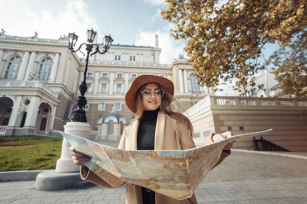 Herfst toerisme. jonge aantrekkelijke vrouwelijke reiziger wordt geleid door de stadsplattegrond. mooi meisje op zoek naar richting in de europese stad. vakantie en toerisme concept