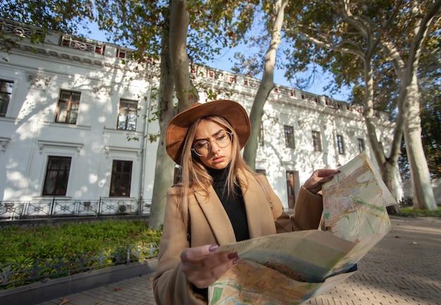 Herfst toerisme. jonge aantrekkelijke vrouwelijke reiziger wordt geleid door de stadsplattegrond. mooi meisje op zoek naar richting in de stad. vakantie en toerisme concept