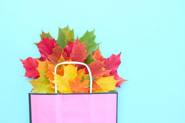 Herfst uitverkoop. papieren zak met herfst esdoorn bladeren.