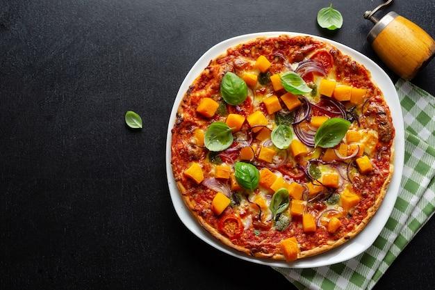 Herfst vegetarische pizza met pompoen en groenten op donkere achtergrond.