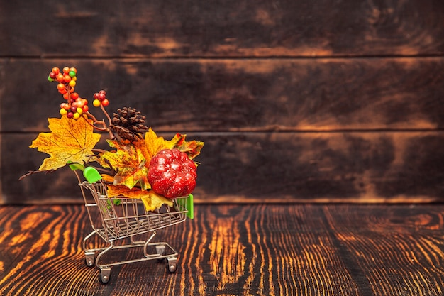 Herfst verkoop. winkelwagen op houten ondergrond met herfstdecor - esdoornbladeren, kegels, bessen, pompoen.